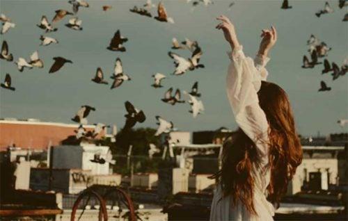 Kvinde udenfor med mange fugle