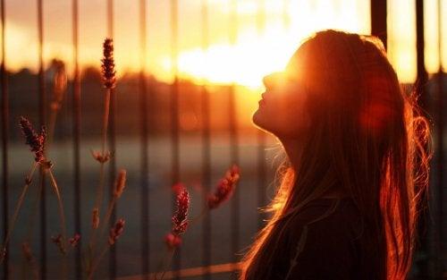 Kvinde der staar udenfor ved solnedgang