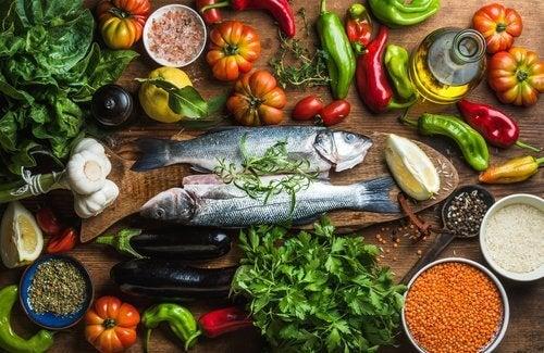 Frisk fisk og groentsager på et bord.