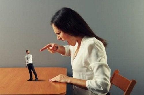 Kvinde råber af lille mand som symbol for verbalt misbrug