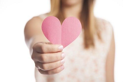 Kvinde der staar med et papir hjerte