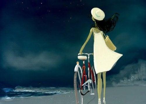Kvinde der gaar med sin cykel - vaere aerlig