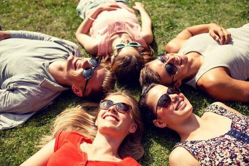 Venner ligger sammen på græsset