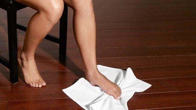 Kvinde laver håndklæde øvelse.