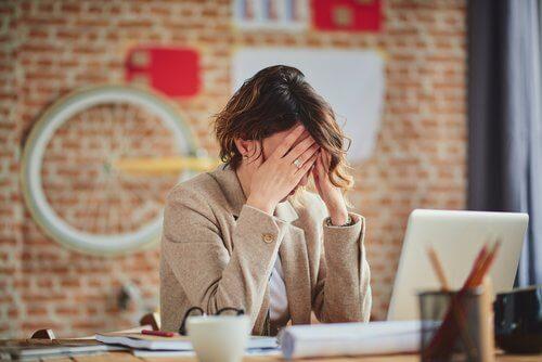 Kvinde der sidder foran computeren med hovedpine