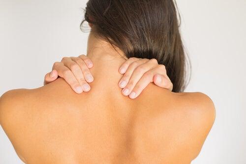 Kvinde masserer sin nakke.