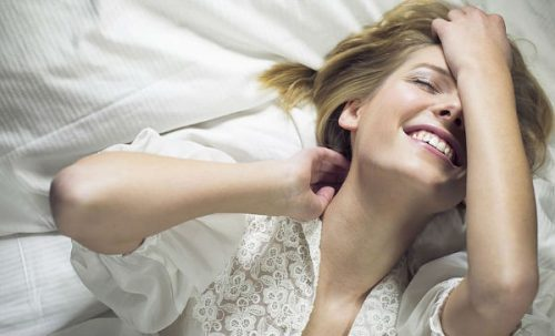 Kvinde paa seng er glad paa grund af kvindelig onani