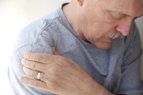 Mand holder sig til sin arm