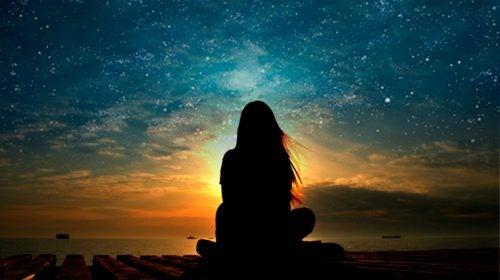 Kvinde sidder og ser solnedgang