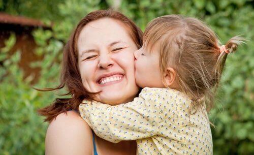 Lille pige kysser sin mor på kinden