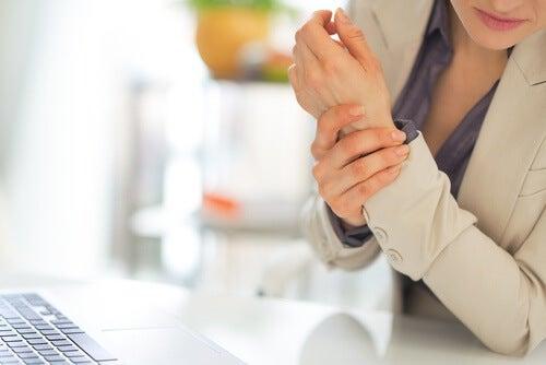 Kvinde holder sig på håndledet
