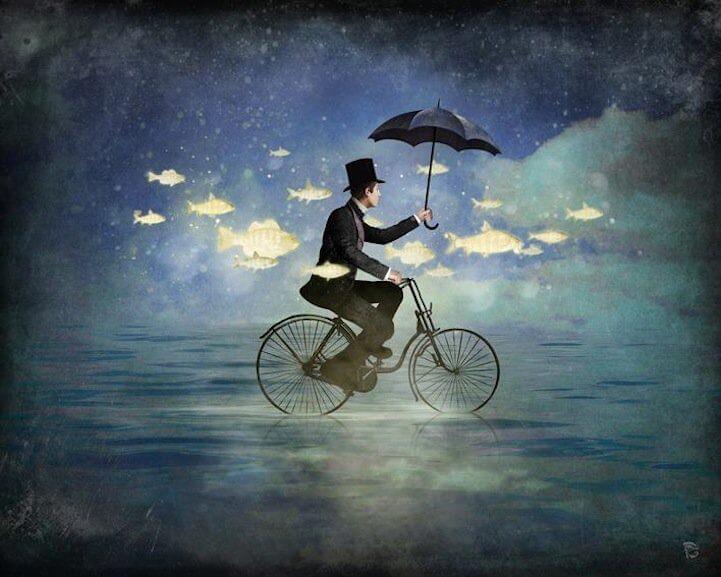 Mand der cykler med paraoly og flyvende fisk