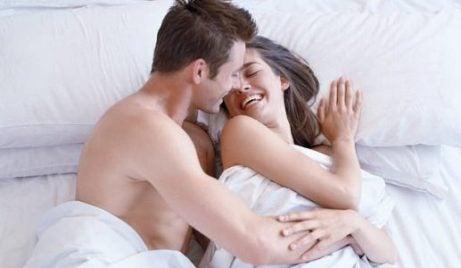 Smilende par i seng