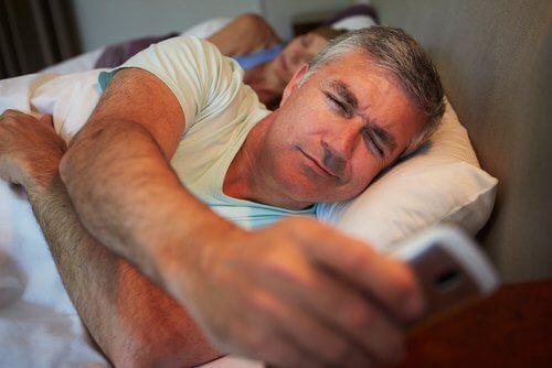 Mand ser på telefon i sengen i stedet for at sove
