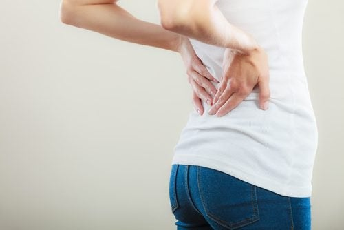 Kvinde med smerter i ryggen