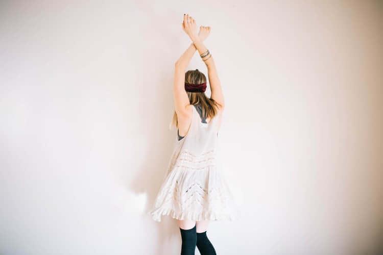 Kvinde der staar med haenderne over hovedet