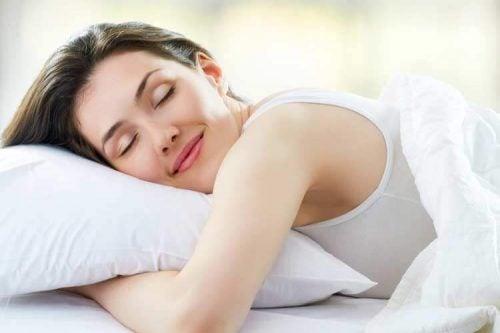 Kvinde der smiler mens huns ligger med sin hovedpude