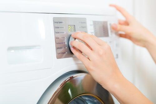 Kvinde der taender vaskemaskinen