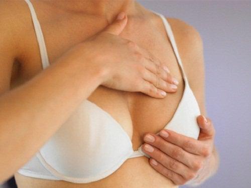 Kvinde der trykker sig paa brystet