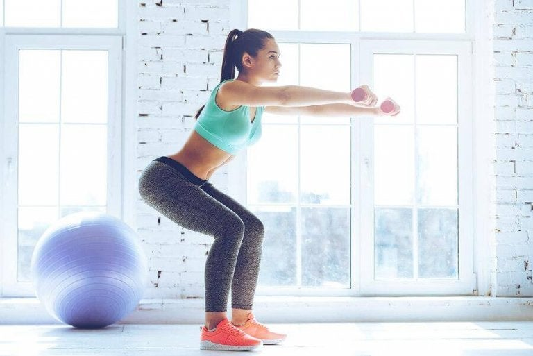 Kvinde der laver squats med haandvaegte