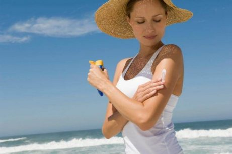 Kvinde der smoerer solcreme paa