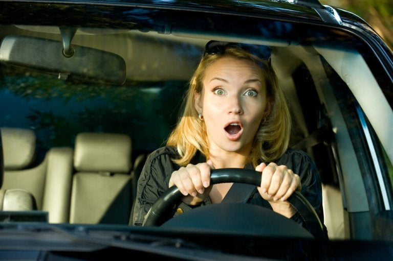 Kvinde der koerer bil med aaben mund - bange for at koere