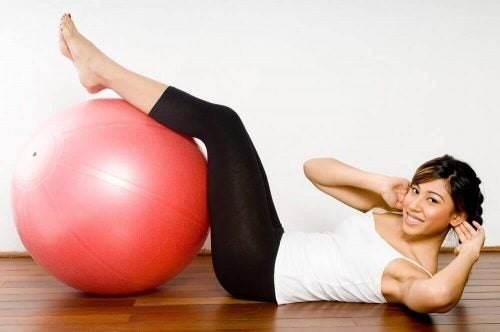 Ung kvinde der laver maveoevelse med en bold