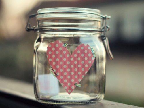 Glaskrukke med lykke har hjerte klistret paa