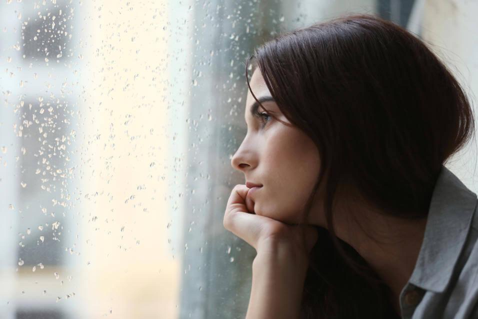 Kvinde der stirrer ud af et vindue med regn paa