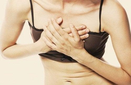 Kvinde der tager sig til brystet pga smerter