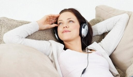 Kvinde der ligger og hoerer musik