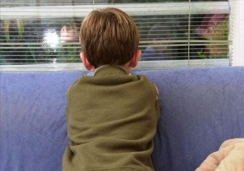 Dreng kigger ud af vindue - identificerer en boernemishandler