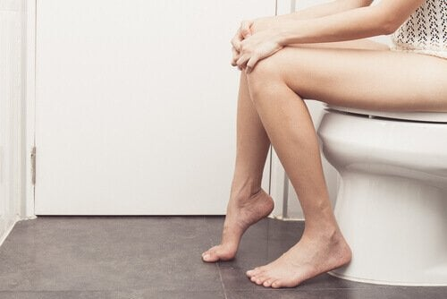 Kvinde der sidder paa toilettet