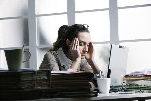 Kvinde med hovedpine paa arbejdet