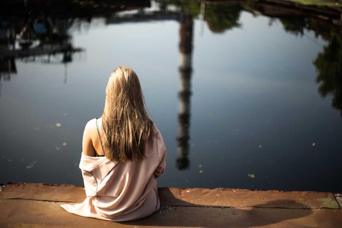 Kvinde der sidder ved vandet