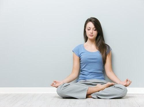 Kvinde der sidder i lotus position