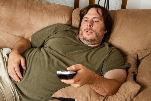 Mand sidder i sofaen