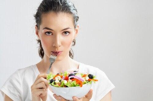 Kvinde spiser salat - epigastralgia