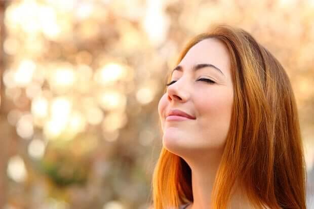 Kvinde der staar med lukkede oejne og smiler