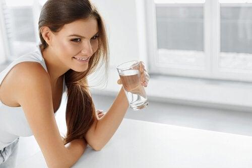 Kvinde der drikker vand - tegn paa vaeskeretention