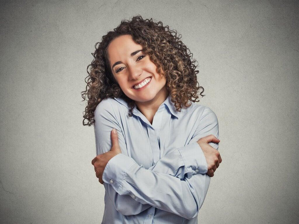 Kvinde der smiler og krammer sig selv