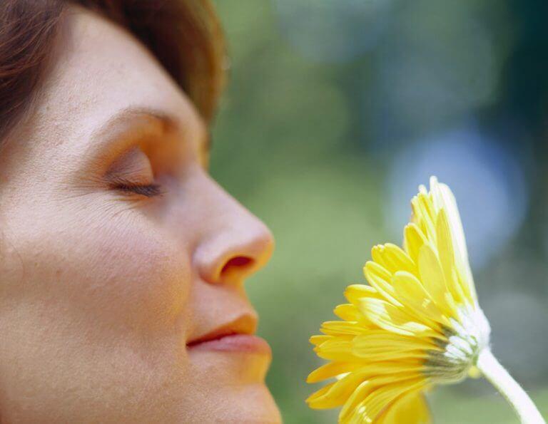 Kvinde der dufter til blomst