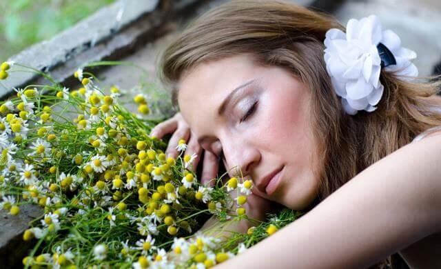 Kvinde der ligger med lukkede oejne ved nogle blomster