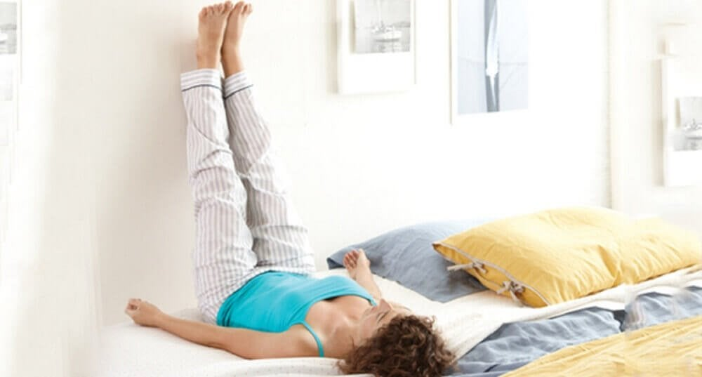 Kvinde ligger på ryggen med benene op