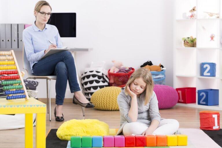Pige der sidder paa gulvet med en kvinde bag sig