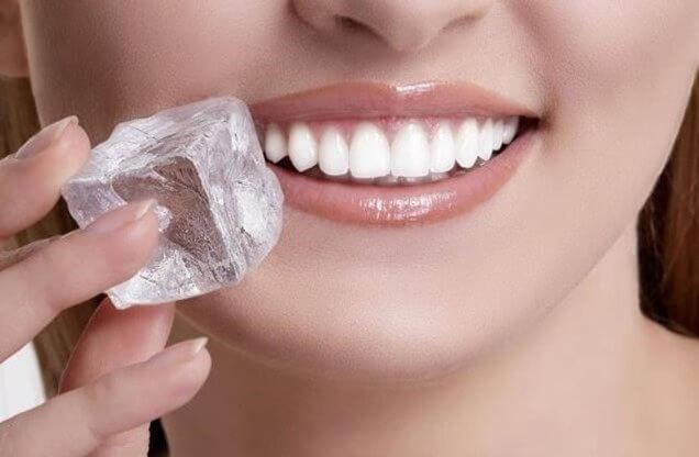 Kvinde der holder en isterning op til munden - hele blister