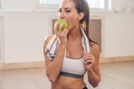Kvinde spiser aeble