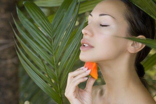 Kvinde der smoerer papaya paa sin hals