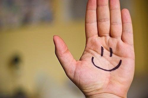 Flad haand der har en paategnet glad smiley