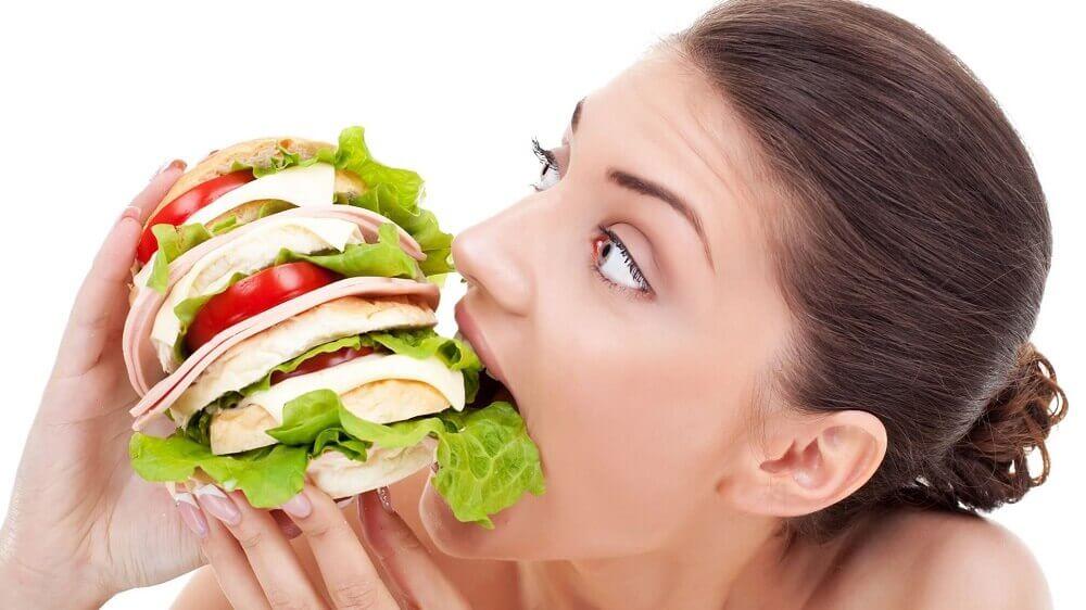 Kvinde spiser kæmpe sandwich